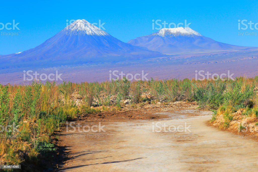 Country dirt road to Dramatic Landscape: Licancabur and Miniques snowcapped volcanoes and Idyllic Atacama Desert steppe, Volcanic landscape panorama – San Pedro de Atacama, Chile, Bolívia and Argentina border stock photo