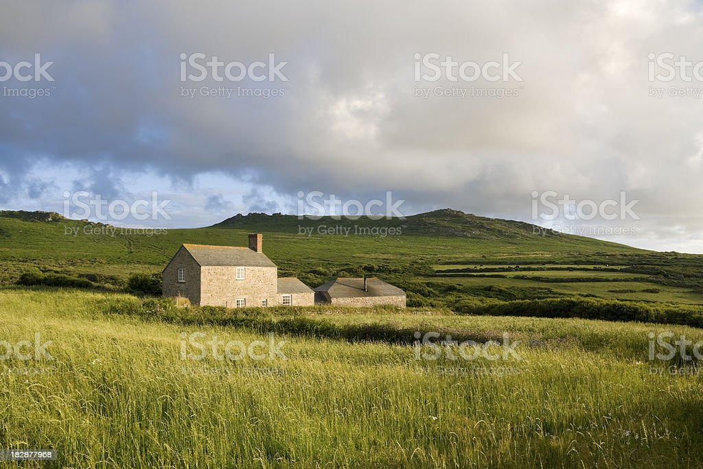 Country farm house in a grassy field near moorland stock photo