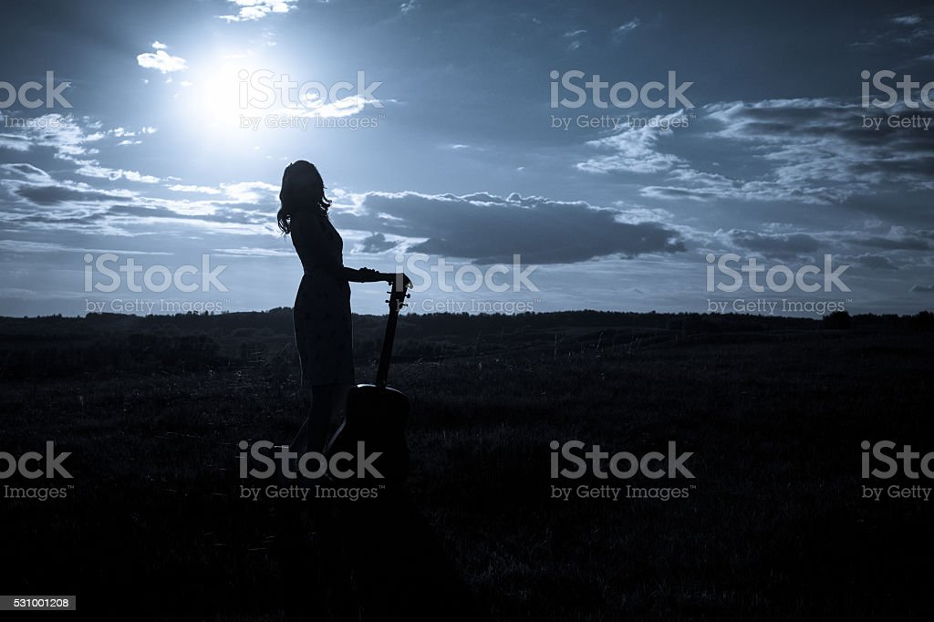 Country girl with guitar at field stock photo