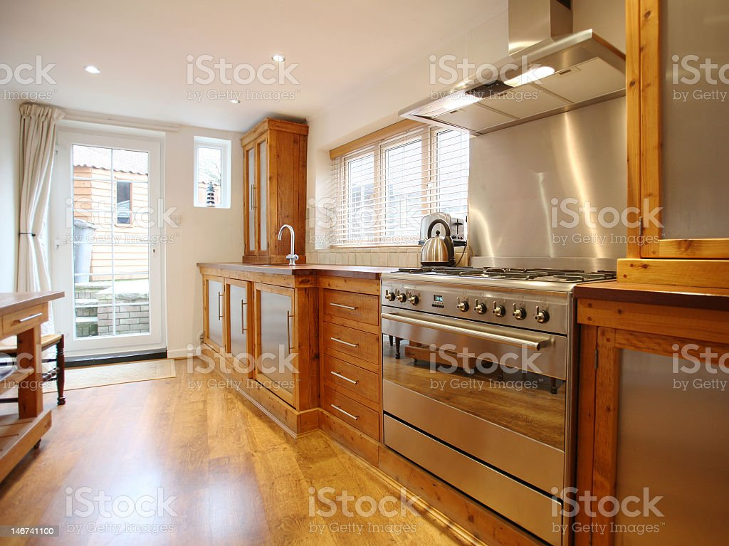 Country kitchen with large stainless steel oven lots of wood stock photo