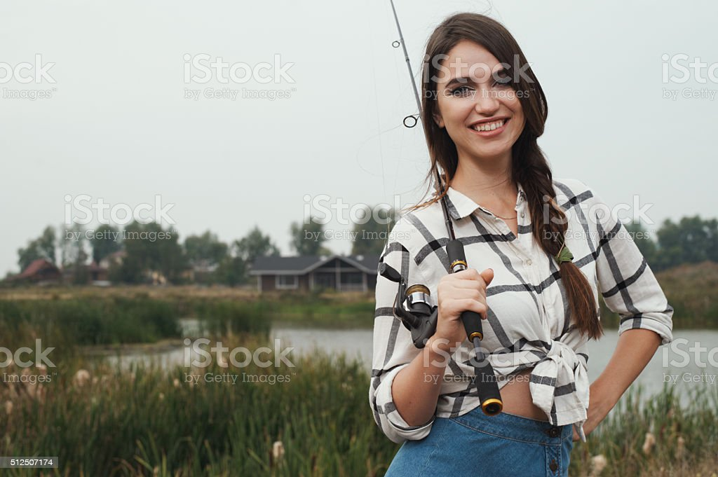 country lady standing against pond on ranch with fish-rod stock photo