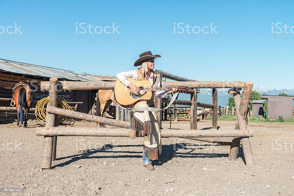 Country Music Cowgirl playing Guitar Horse Stable Ranch Montana USA stock photo