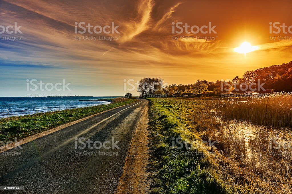 Country road and sunset by the sea stock photo