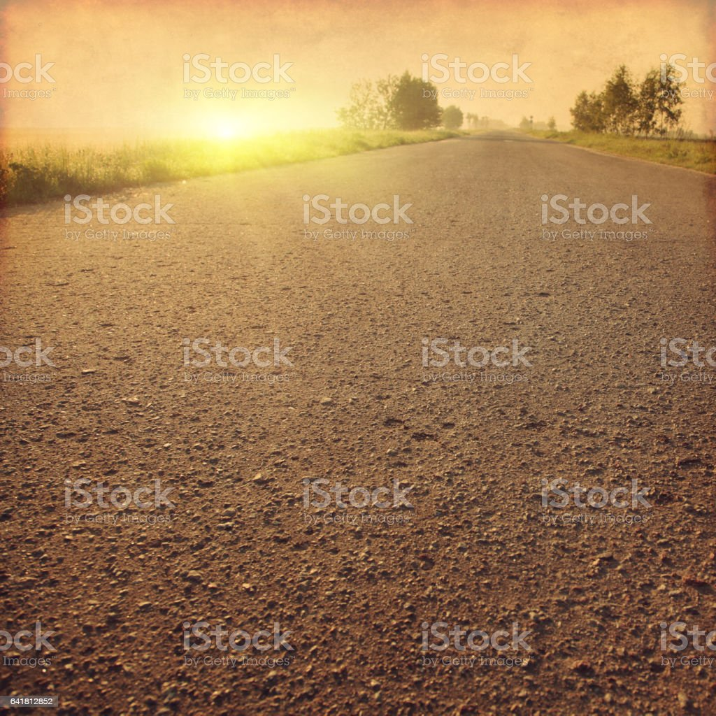 Country road at sunset in grunge and retro style. stock photo