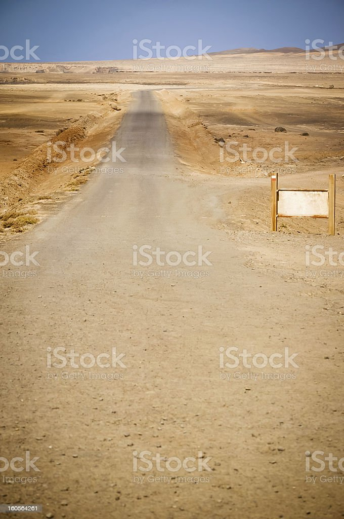 Country road, blank billboard and desert landscape royalty-free stock photo