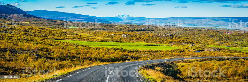 Country road curving down into green valley farms villages panorama stock photo