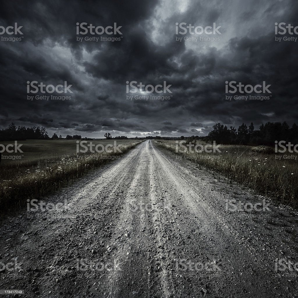 Country road in a field at storm stock photo