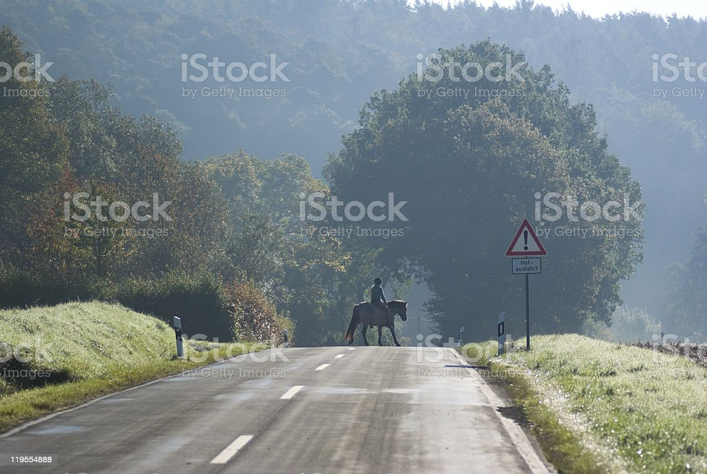 Country road in autumn with a horsewoman stock photo