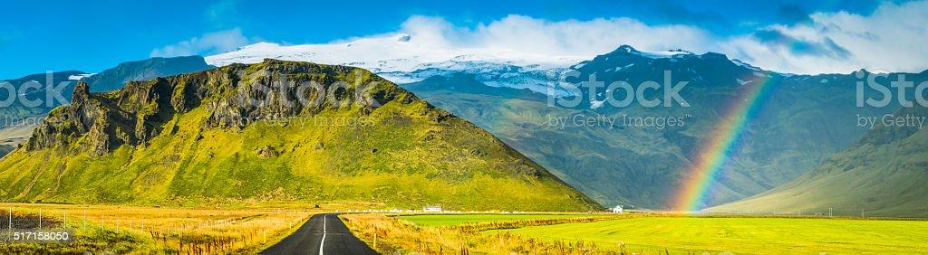 Country road rainbows green pasture white mountain peaks panorama Iceland stock photo