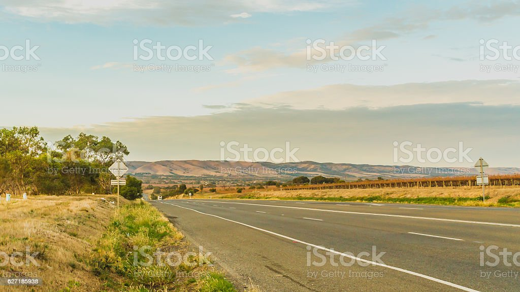country road surrounded by mountains and vineyards stock photo
