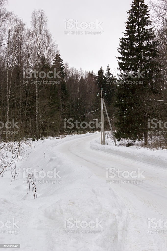 country road turn in snowy winter forest stock photo