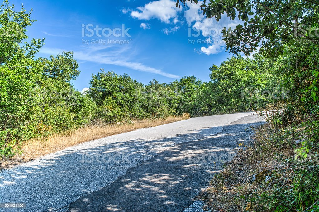 country road under a blue sky stock photo