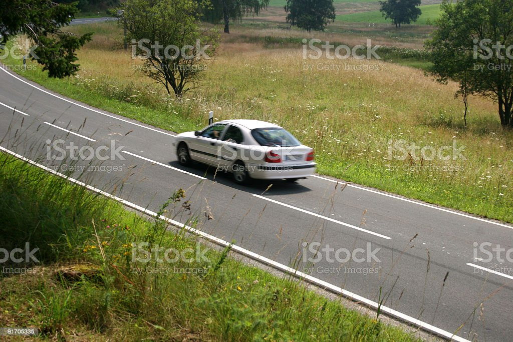Country road with a car on the move royalty-free stock photo