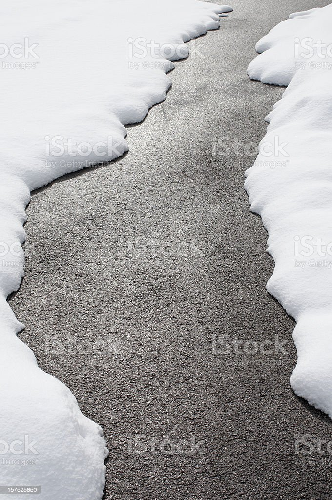 Country road with melting snow on either side  stock photo