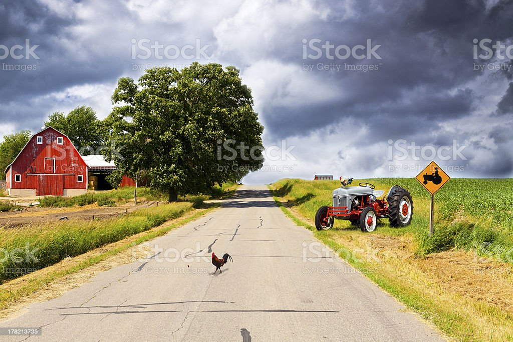Country Road With Red Barn and Tractor On Side stock photo