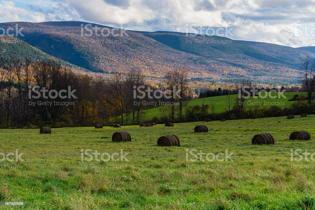 Countryside and Haystacks under Cloudy Sunset stock photo