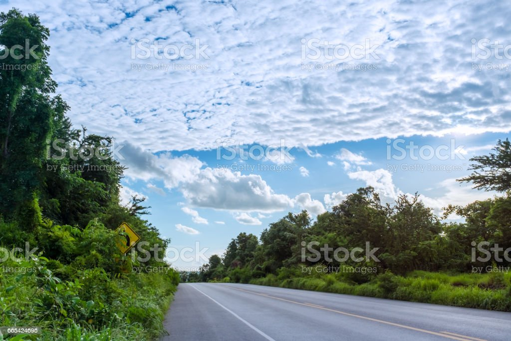 Countryside highway against sky and cloudy, bypass a green forest. stock photo