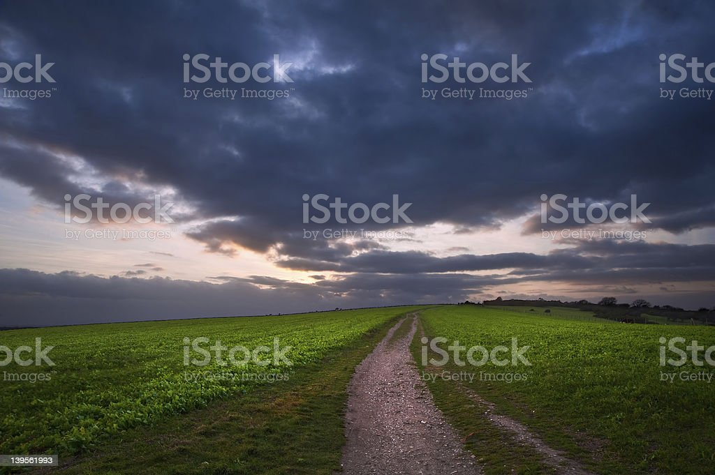 Countryside path leading through fields towards dramatic sky royalty-free stock photo