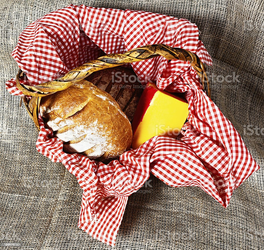 Country-style picnic: bread and cheese in gingham-lined basket royalty-free stock photo