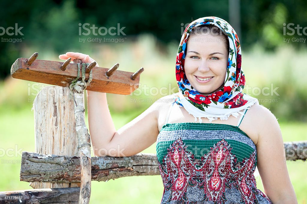 Countrywoman holding wooden rake. Summer in village royalty-free stock photo