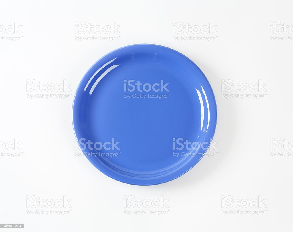 Coupe shaped blue ceramic plate stock photo