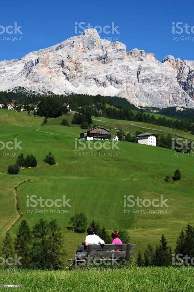 A couple admires the Sasso della Croce group in the Dolomites. Alta Badia, Italy. stock photo