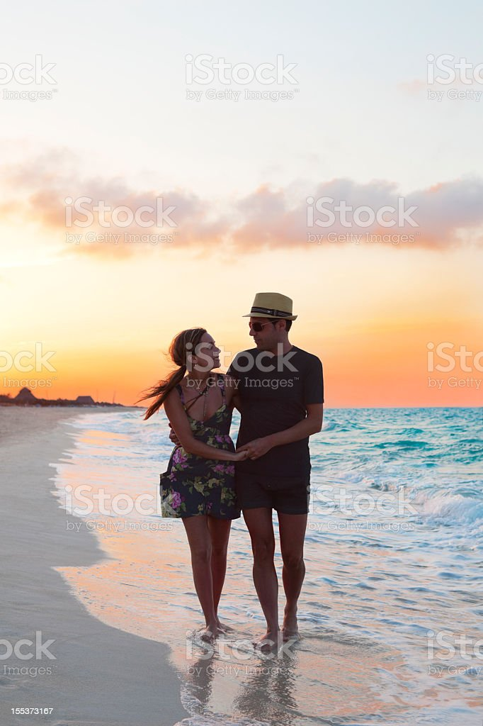 Couple After Sunset Walking Along The Beach royalty-free stock photo