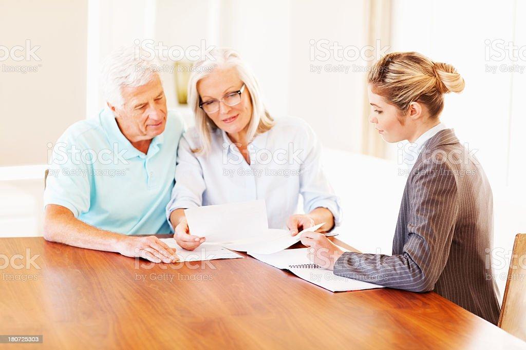 Couple Analyzing Investment Scheme With Advisor royalty-free stock photo