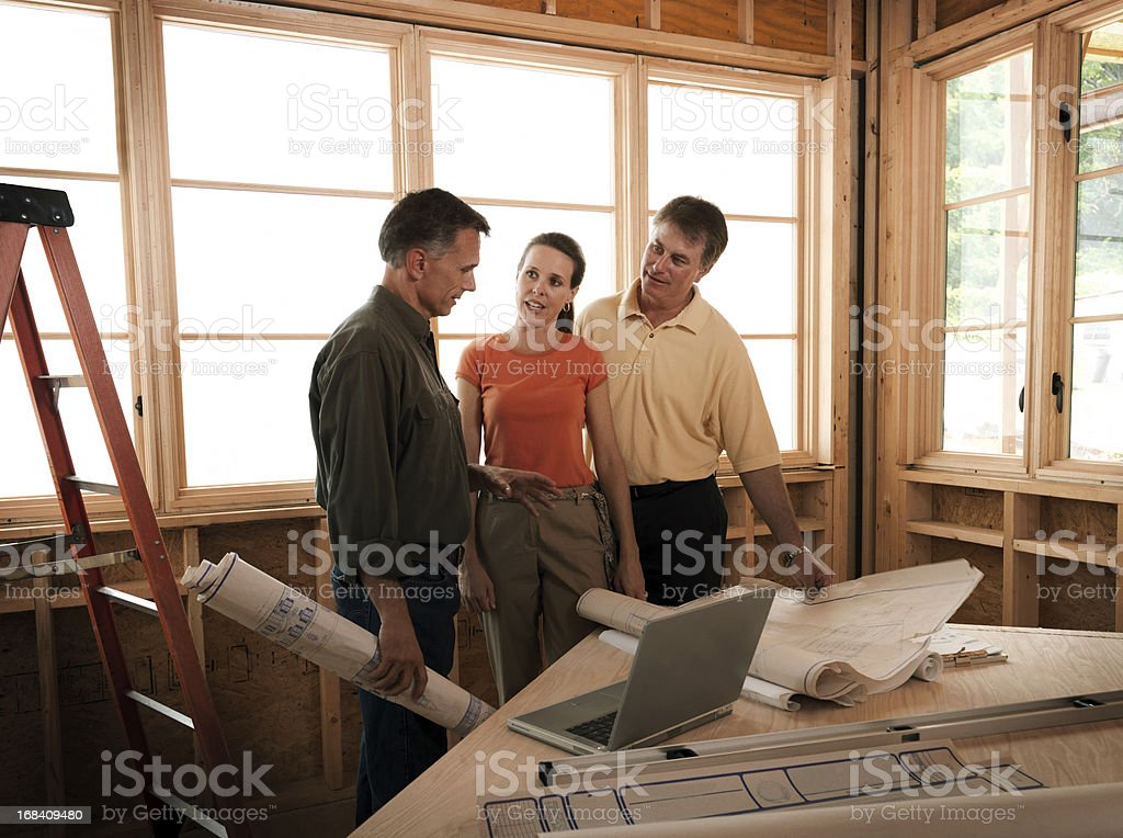Couple and Builder at Construction Site stock photo