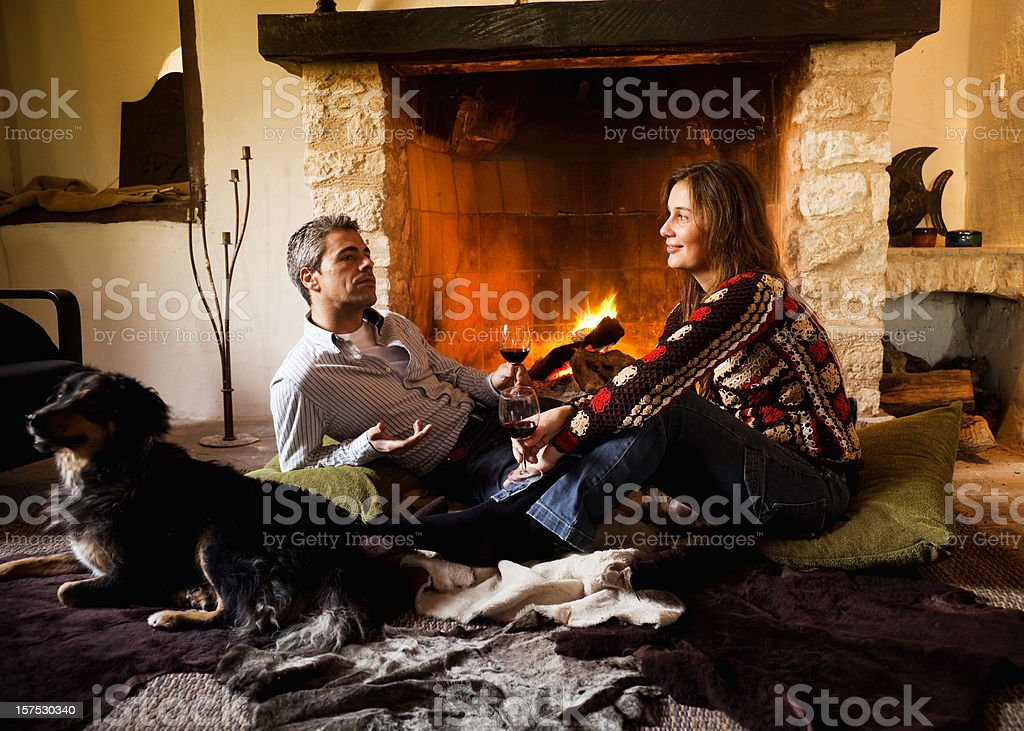Couple and dog by the fire royalty-free stock photo