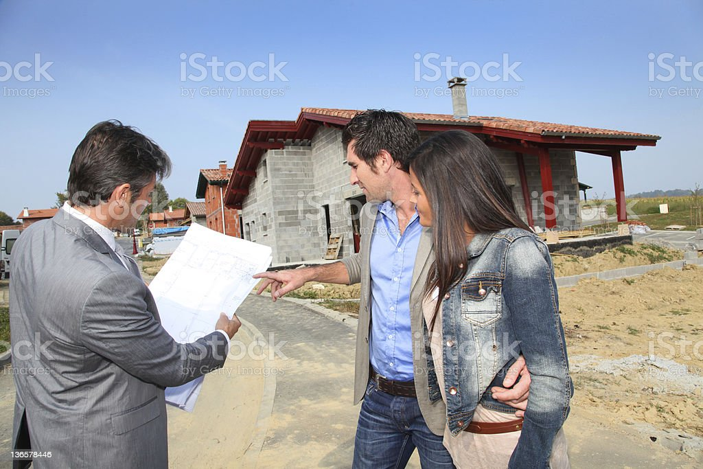 Couple and salesman on construction site royalty-free stock photo
