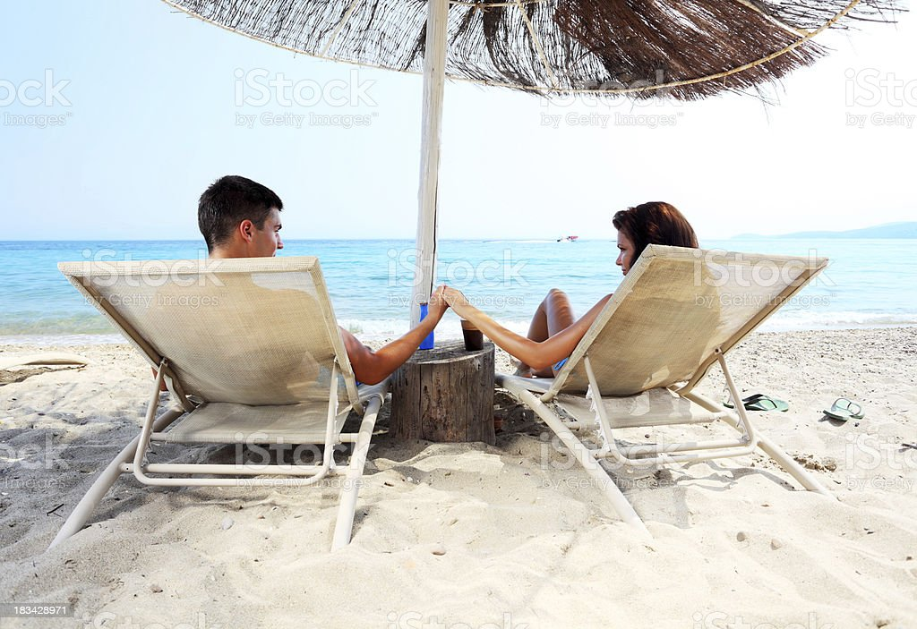 Couple are sitting on chaise longue  and enjoying royalty-free stock photo