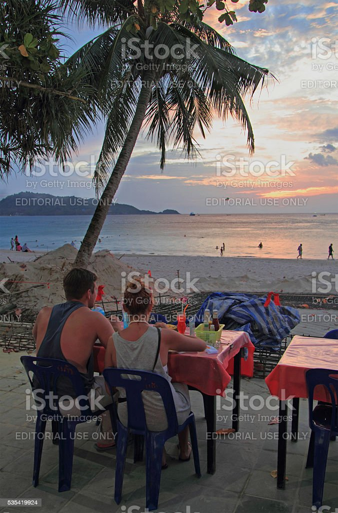 couple are watching sunset at the Patong beach, Thailand stock photo