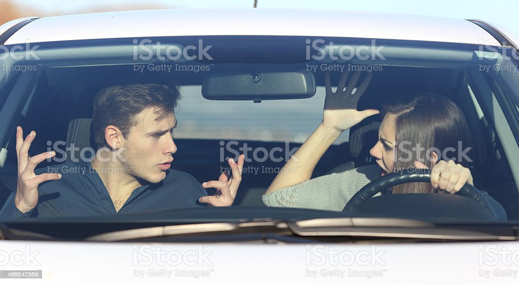 Couple arguing while she is driving a car stock photo