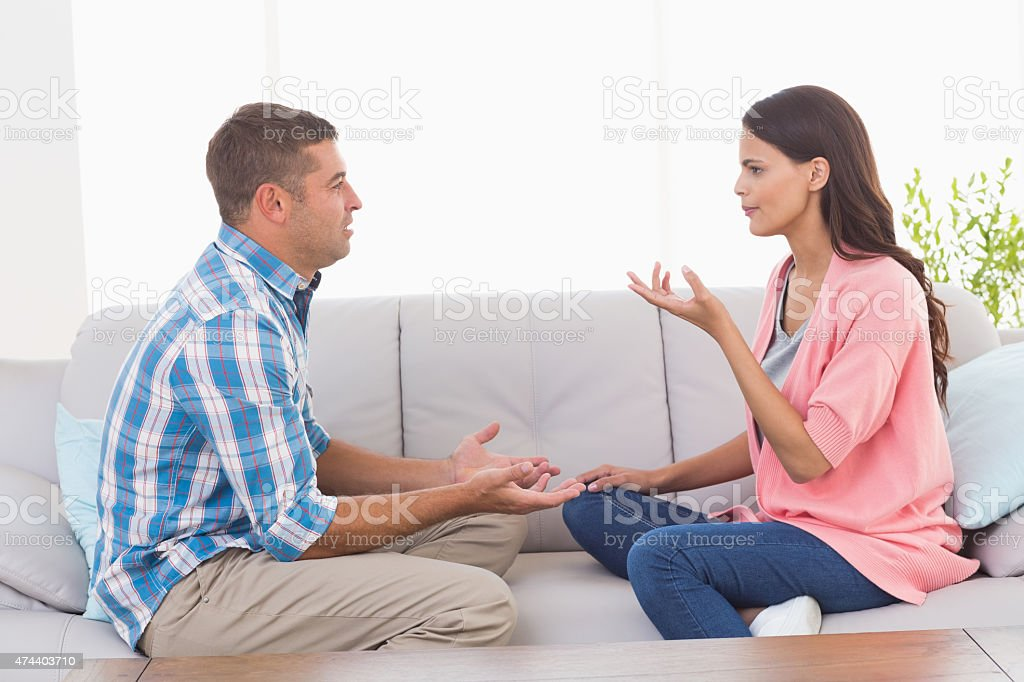 Couple arguing while sitting on sofa stock photo