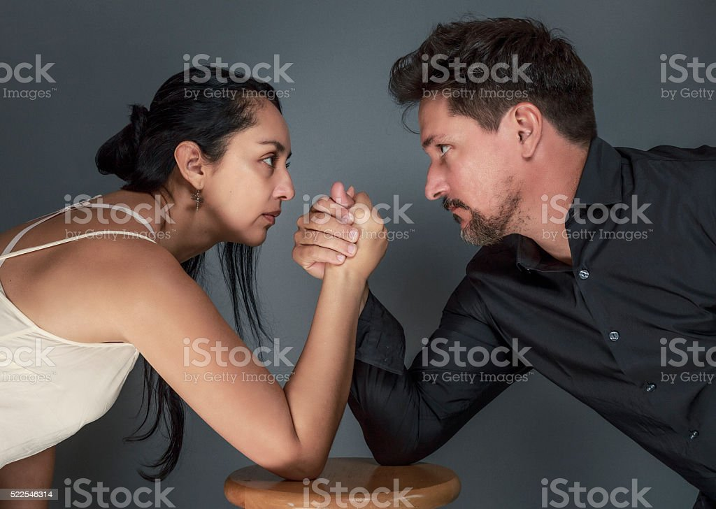 Couple Arm Wrestling Against Dark Background stock photo