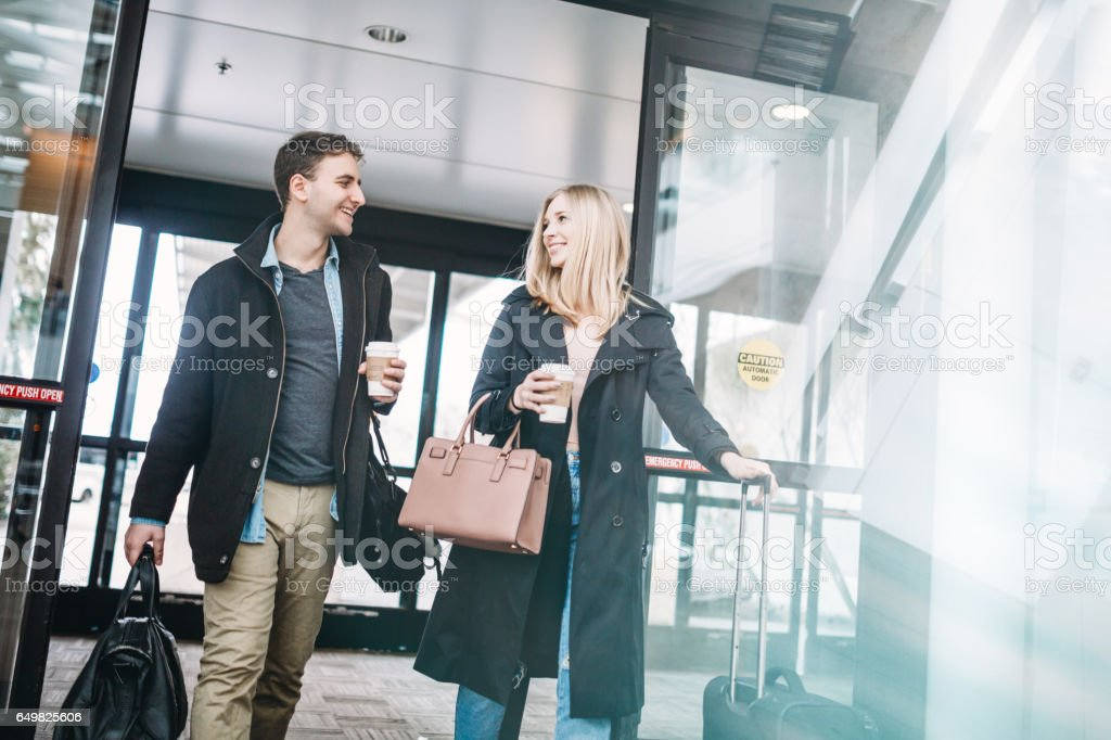 Couple Arriving at Airport Terminal stock photo