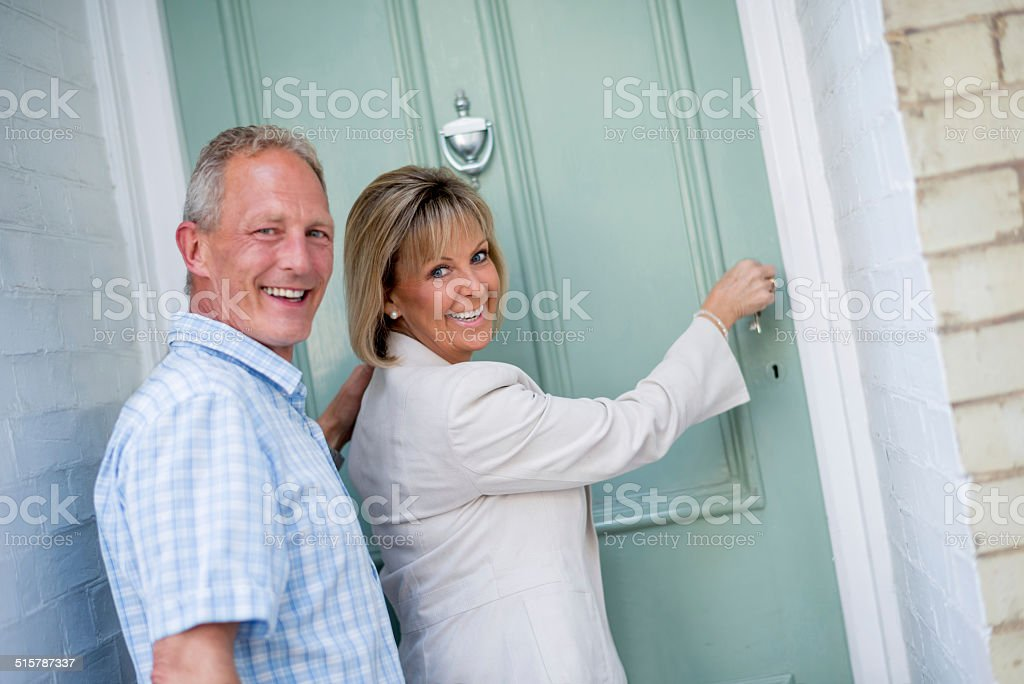 Couple arriving home stock photo
