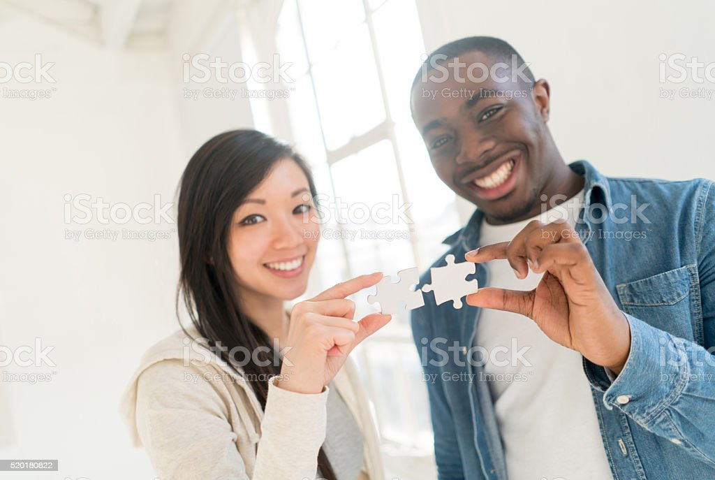 Couple assembling a puzzle stock photo