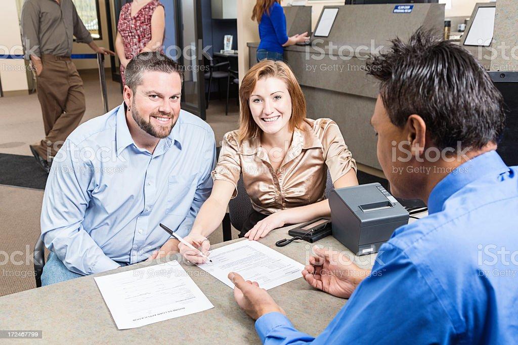 A couple at a bank looking at an application royalty-free stock photo