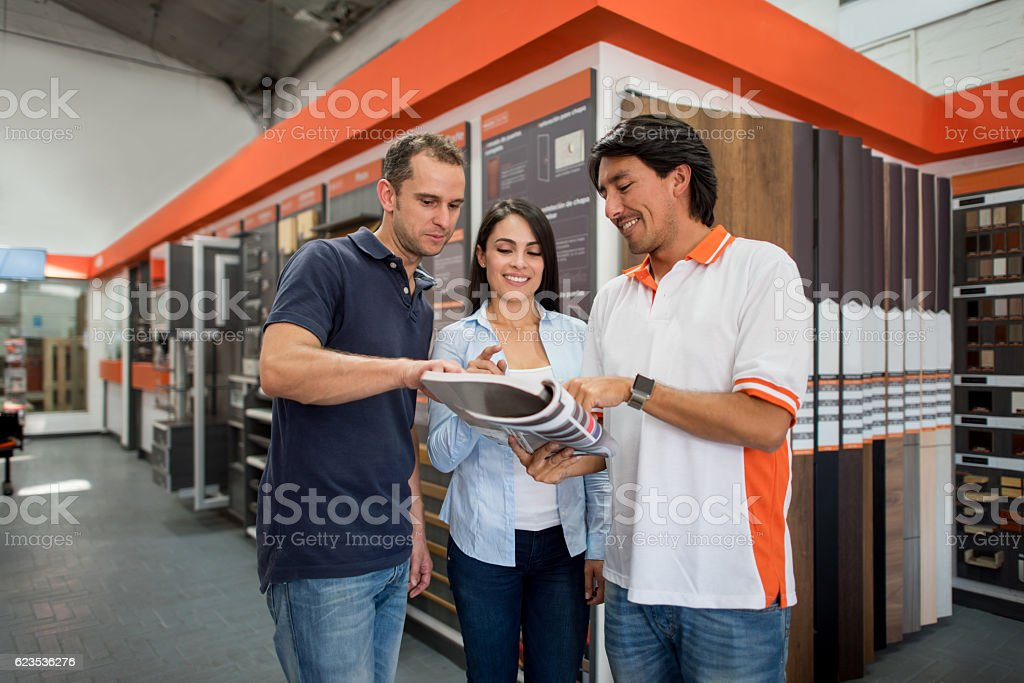 Couple at a flooring store talking to salesman stock photo