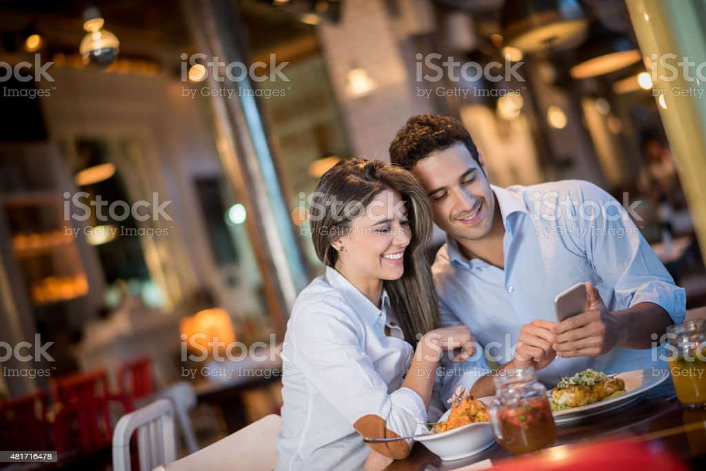 Couple at a restaurant looking at a cell phone stock photo