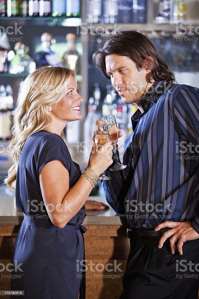 Couple at bar drinking champagne stock photo