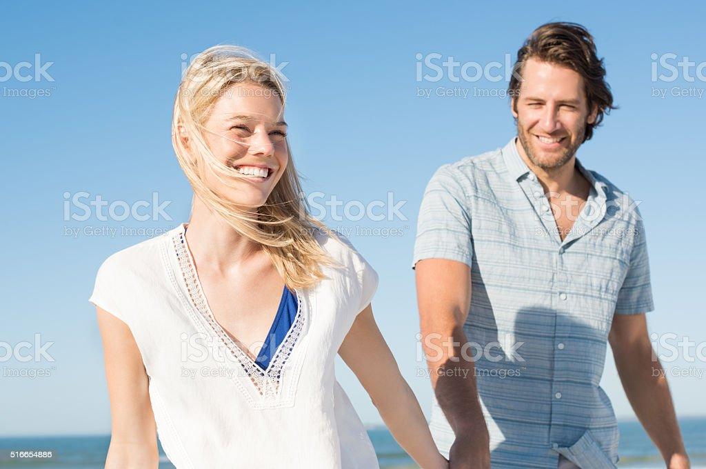 Couple at beach walking stock photo