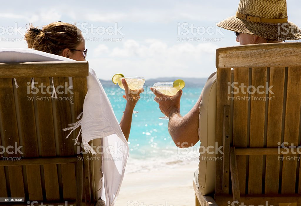 Couple at Caribbean beach with margarita cocktails royalty-free stock photo