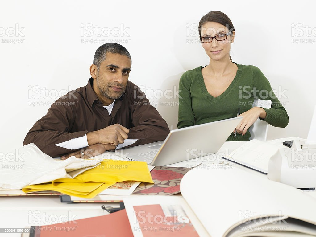 Couple at desk by laptop computer and samples, smiling, portrait royalty-free stock photo