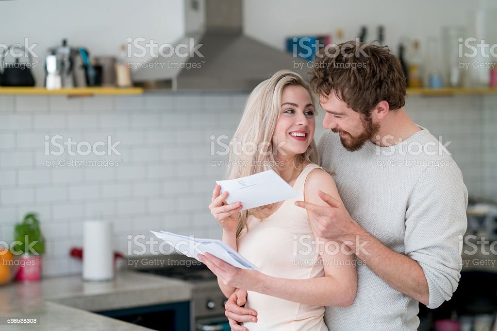 Couple at home checking the mail stock photo