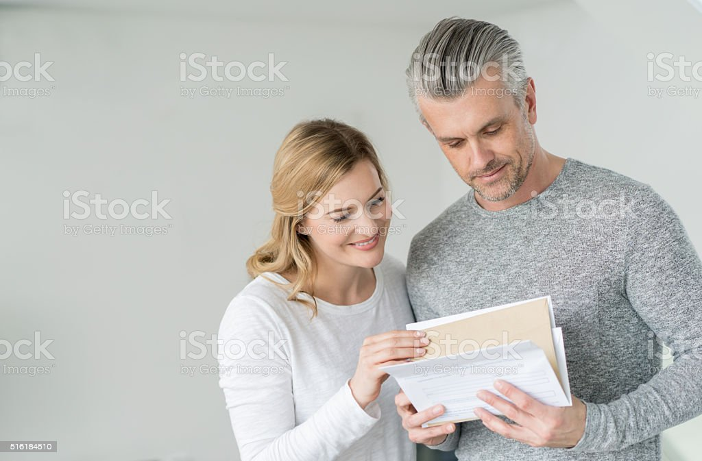Couple at home getting the mail stock photo