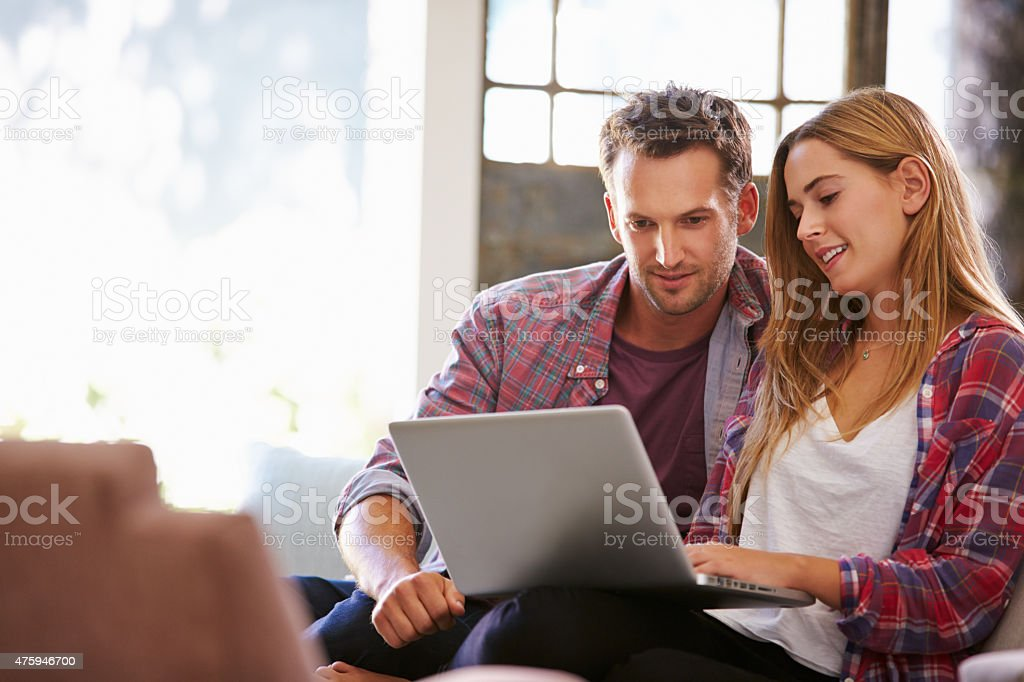 Couple At Home In Lounge Using Laptop Computer stock photo