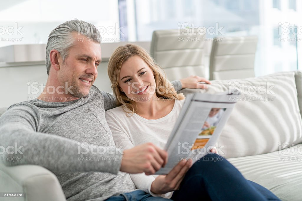 Couple at home reading a magazine stock photo